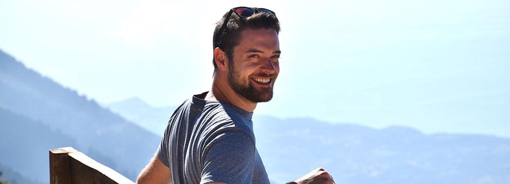 Philipp Marenne auf einer Bank mit Bergen im Hintergrund